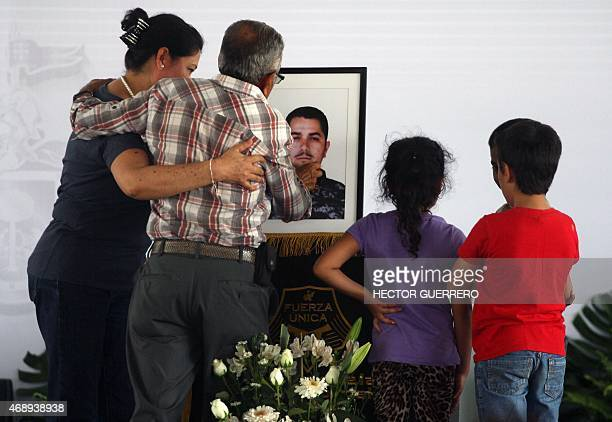 Realtives of one of the 15 police members killed during an ambush by criminal gang assassins on April 6 mourn next to his coffin during the funeral...