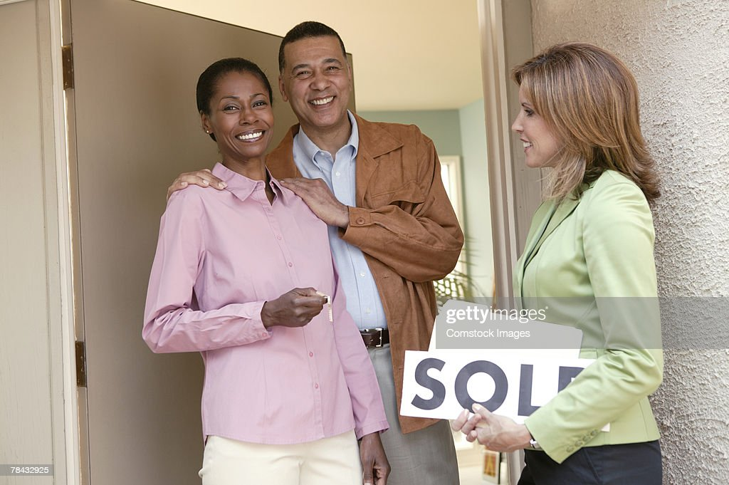 Realtor and couple at new home : Stockfoto