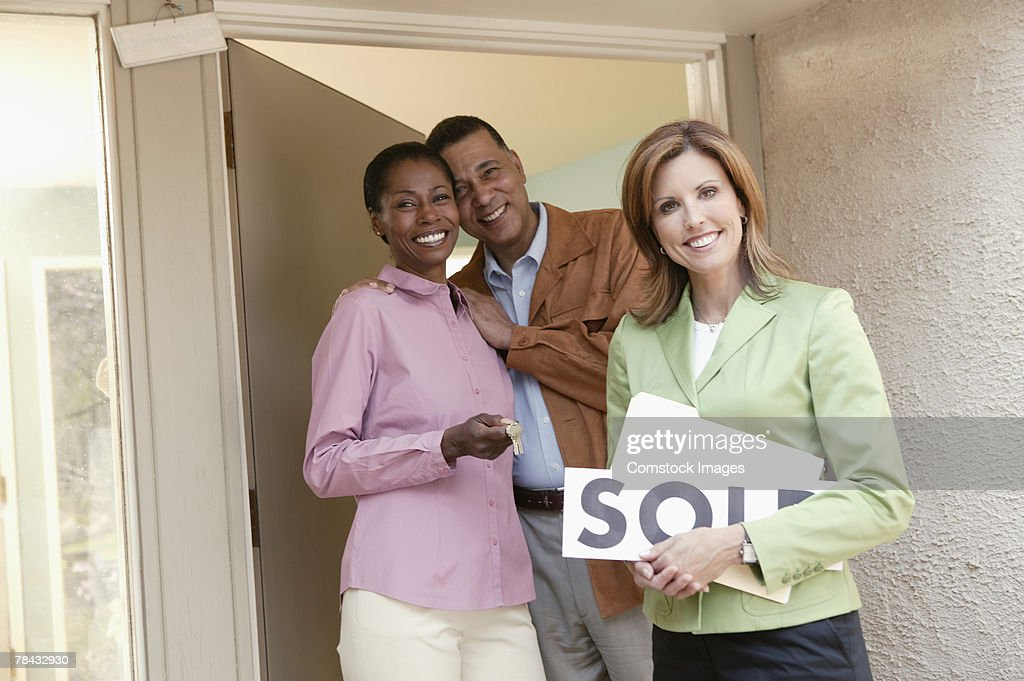 Realtor and couple with new home : Stockfoto