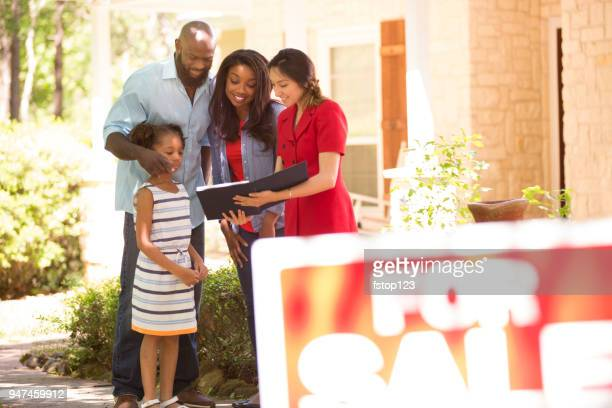 realtor and family looking at new home to purchase. - selling stock pictures, royalty-free photos & images