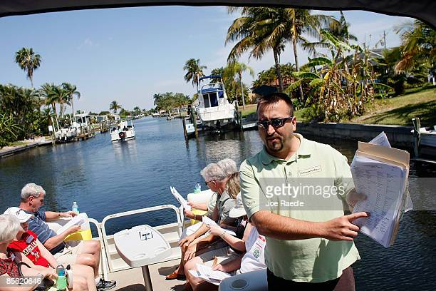Realtor Bill Mitchell explains some of the properties to prospective buyers taking part in a foreclosure boat tour by Foreclosures 'R Us realty...