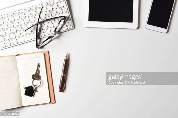 Realtor company office work desk top view with home key, computer keyboard, tablet, smart phone white background
