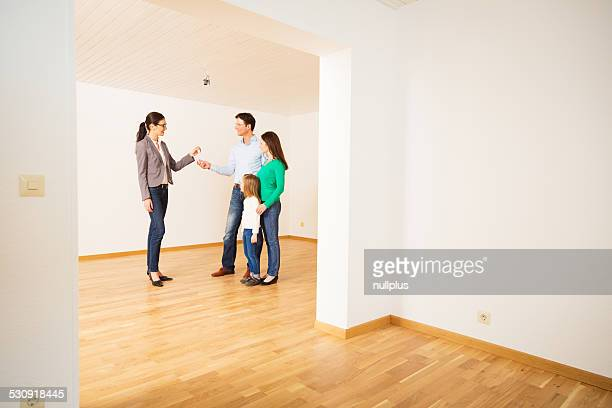 realtor giving customers the key to their new flat