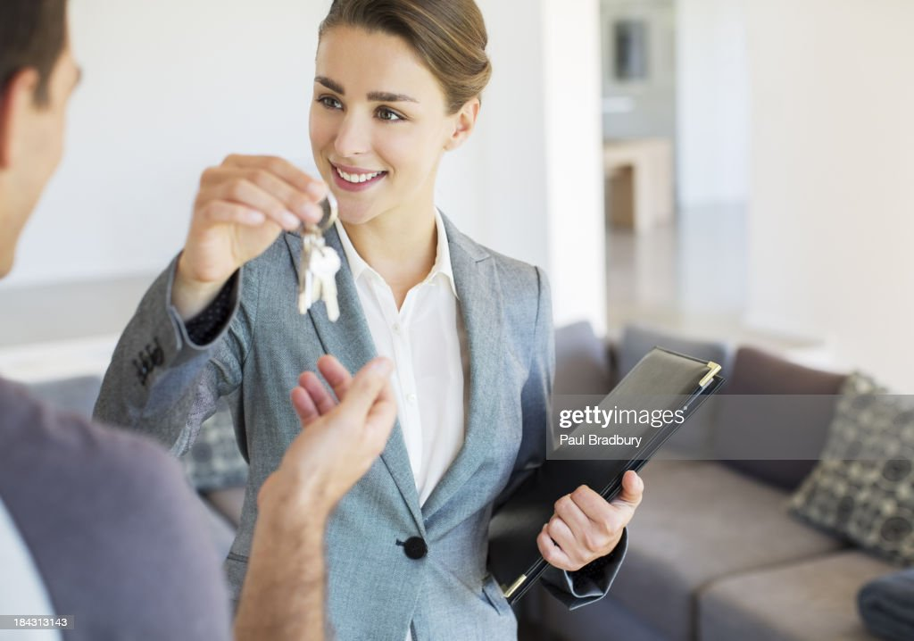 Realtor giving man keys to new house : Stock Photo
