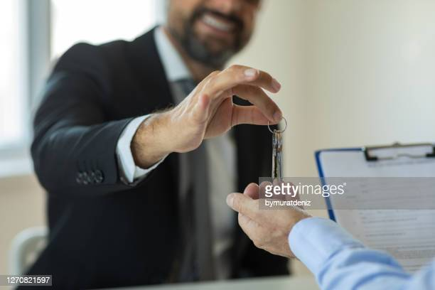 realtor hand giving keys to new house owner - lease agreement stock pictures, royalty-free photos & images
