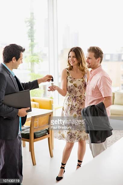 Realtor handing couple keys to home