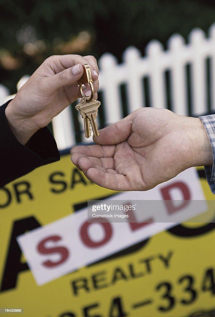Realtor handing house keys to new owner : Stockfoto