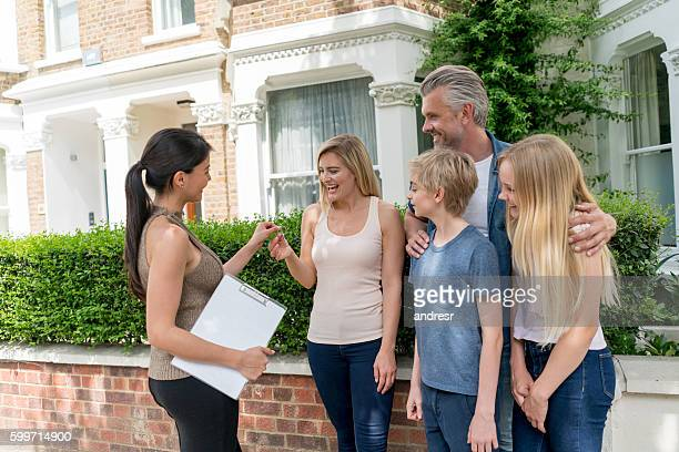Realtor handling house keys to a family