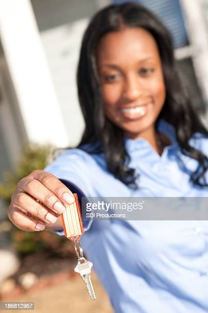Realtor Holding Out House Key to New Home Buyer