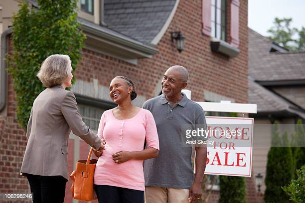 Realtor shaking hands with smiling couple outside house for sale