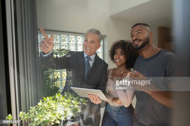 realtor showing a property to an african american couple - real estate broker stock photos and pictures
