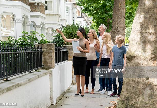 realtor showing house to a family - house rental stock photos and pictures