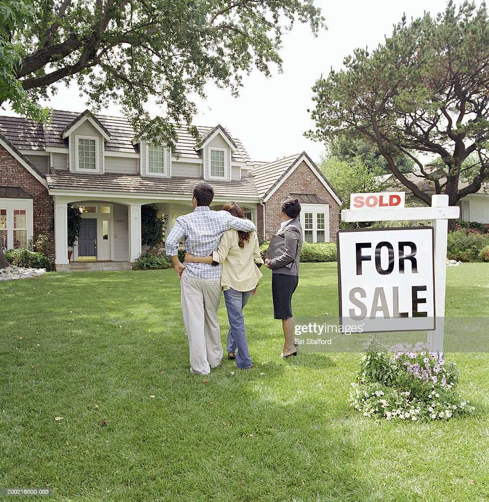Realtor standing with couple in front of house : Stock Photo
