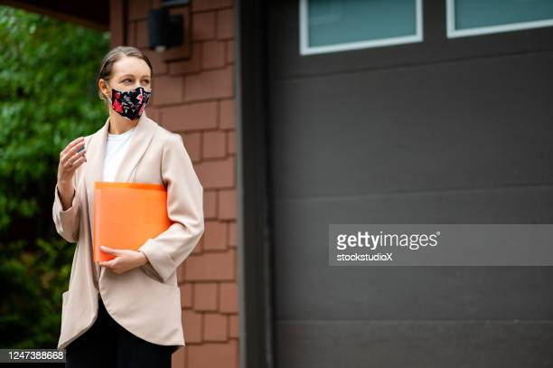 realtor with a protective face mask - real estate stock pictures, royalty-free photos & images