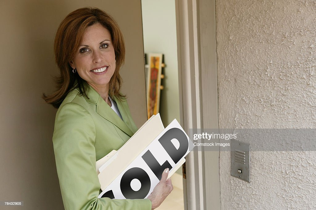 Realtor with SOLD sign opening door to house : Stockfoto