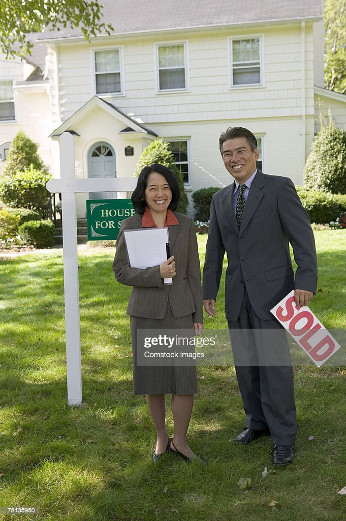 Realty agents with sold sign : Stockfoto