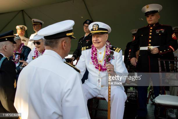 Rear Admiral Darius Banaji US Navy left greets Lieutenant Commander Louis Conter United States Navy the only USS Arizona Survivor in attendance as...