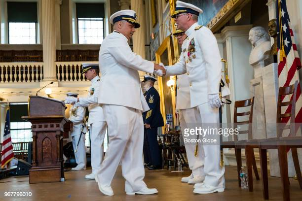 Rear Admiral Steven Poulin right shakes hands with Rear Admiral Andrew Tiongson during a change of command ceremony in which Tiongson relieved Poulin...