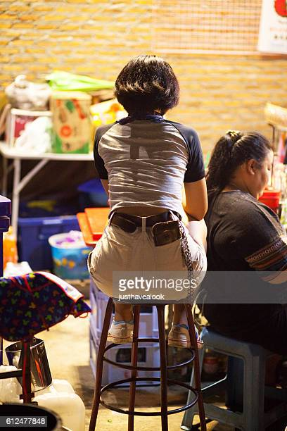 Rear- and backshot of sitting thai girl in hot pants