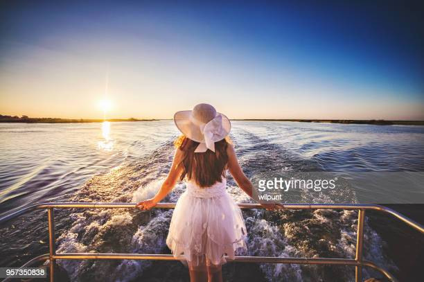 rear angle view female on the back of a moving boat at sunset - hair bow stock pictures, royalty-free photos & images