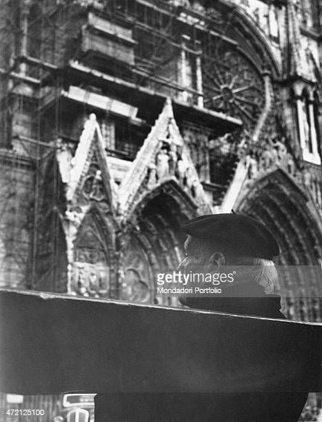 Rear closeup of an old man wearing a beanie sitting on a bench in front of the facade of Notre Dame Cathedral the structure is partially covered with...