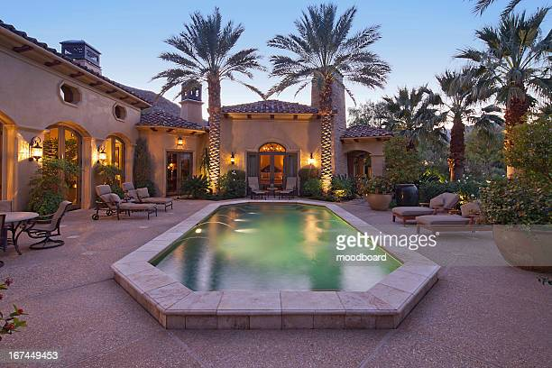 Rear entrance  of luxury villa at night with swimming pool
