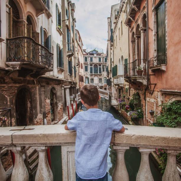 rear image ob boy enjoying canal view in Venice