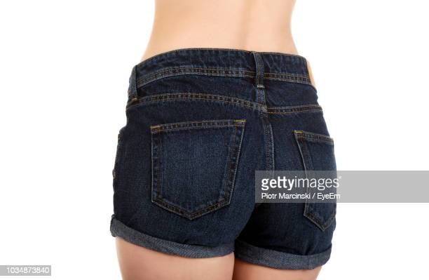 rear midsection of woman wearing hot pants against white background - hands in her pants stock pictures, royalty-free photos & images