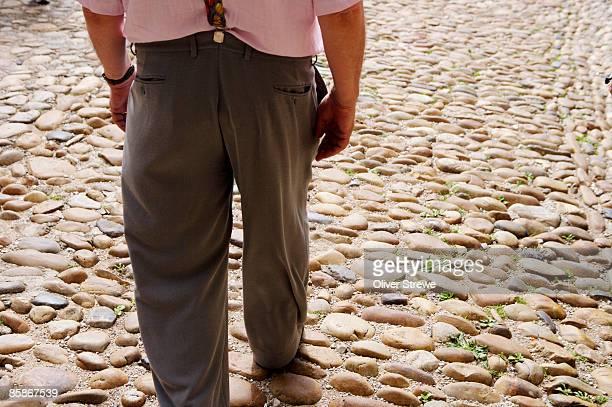 rear of man walking on cobbled street. - lentezza foto e immagini stock