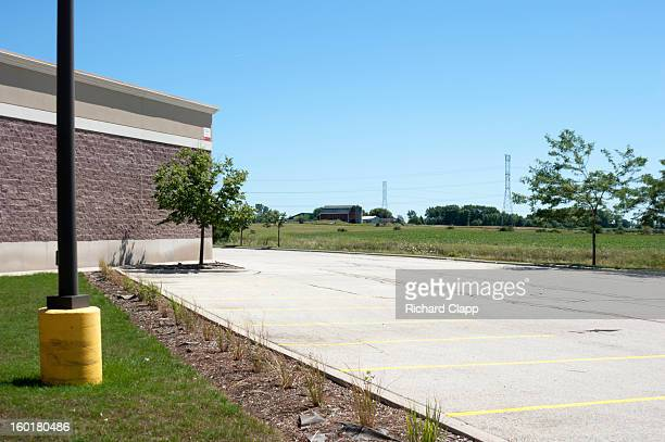Rear of the mall in Sheboygan shows the edge of the urban environment abutting and encroaching upon farmland. The mall building facade, a parking...