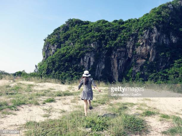 Rear Of Woman Running On Grass Against Mountain