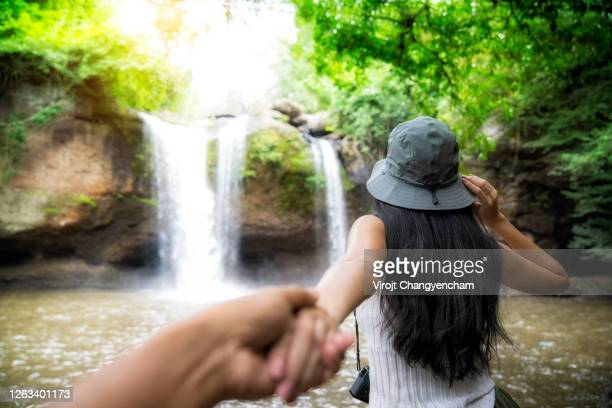 rear of woman wear hat and holding man hand travelling at waterfall of tropical forest in thailand, heo suwat waterfall at khao yai national park, thailand. - thailand stock pictures, royalty-free photos & images