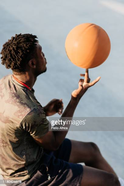Rear profile of cool basket player spinning a ball on his finger