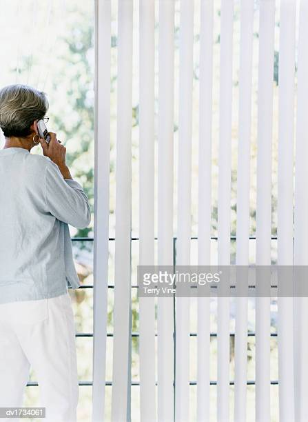 Rear Shot of a Woman Using a Mobile Phone on a Balcony