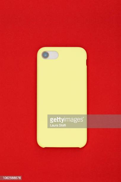 rear sight of smart phone with pale yellow cover against pop red background - covering stock pictures, royalty-free photos & images