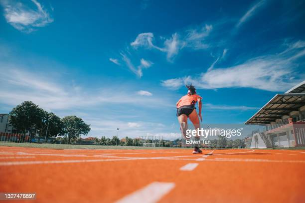 rear view aerodynamic asian chinese female athletes sprint running at track and run towards finishing line in the morning at track and field stadium - track and field stadium stock pictures, royalty-free photos & images