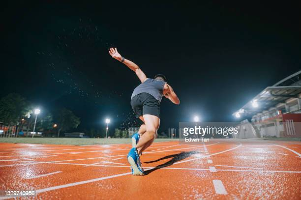 rear view aerodynamic asian chinese male athletes sprint running at track and run towards finishing line at track and field stadium track rainy night - try scoring stock pictures, royalty-free photos & images