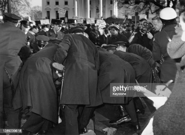 Rear view as police officers restrain a demonstrator during a civil rights protest outside the White House in Washington, DC, circa 1965. The feet of...