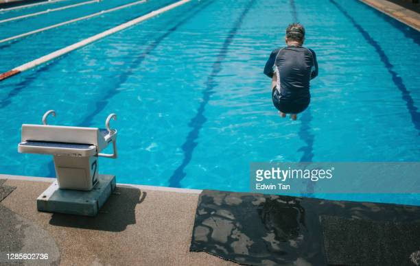 rear view asian chinese active senior man jump dive into the swimming pool - human back stock pictures, royalty-free photos & images