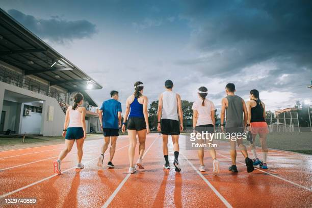 rear view asian chinese sport team walking on track and field after the training at late evening with stormy cloud wet floor - forward athlete stock pictures, royalty-free photos & images