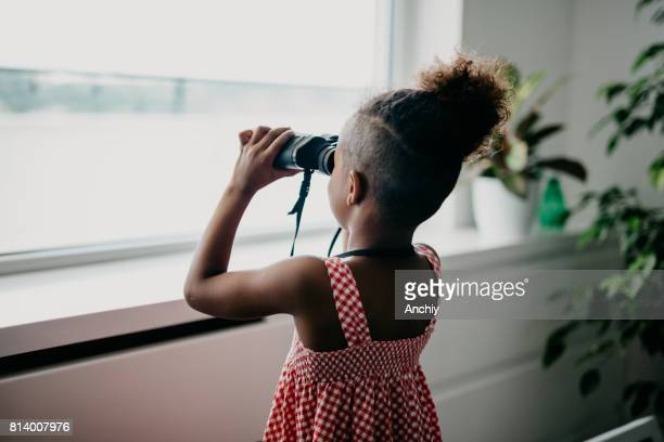 rear view at african kid looking through binoculars - curiosity stock photos and pictures
