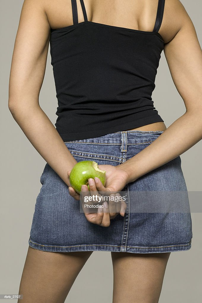 rear view beauty portrait of young adult female in a black tank top as she holds an apple : Stock Photo