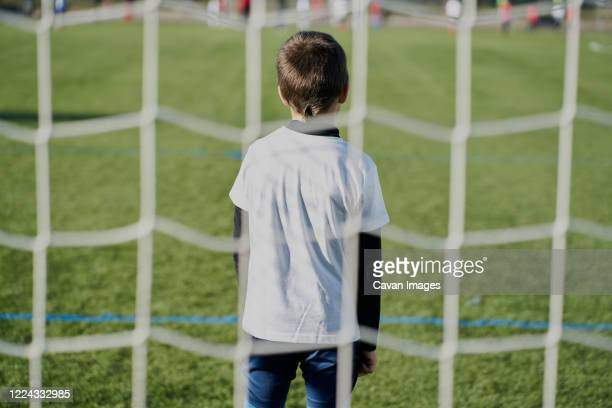 rear view behind the net of a child football goalkeeper in the goal - goalkeeper stock pictures, royalty-free photos & images