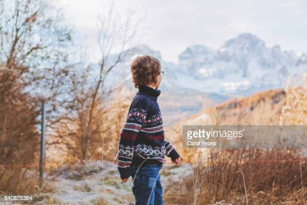 rear view blonde boy standing in front Pyrenees mountains