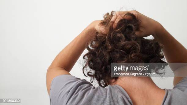rear view close-up of man tying hair against white background - hand in hair stock pictures, royalty-free photos & images