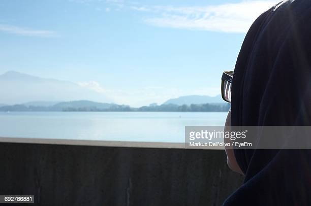 Rear View Close-Up Of Woman Looking At Lake Zug Against Sky