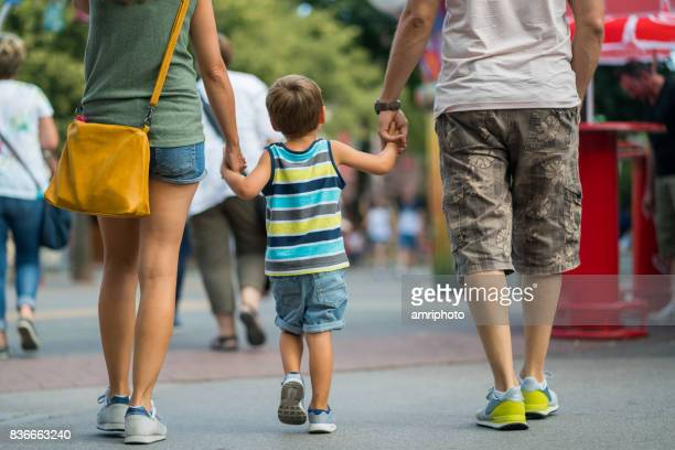 rear view family walking together on summer day in amusement park - arts culture and entertainment stock pictures, royalty-free photos & images