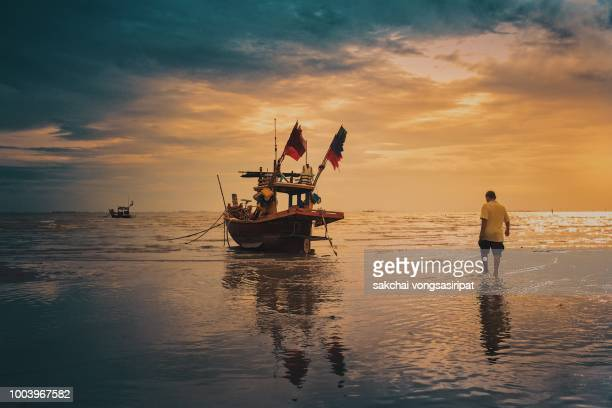 rear view fishermen are walking to the fishing boat against sky during sunset - paesaggio marino foto e immagini stock