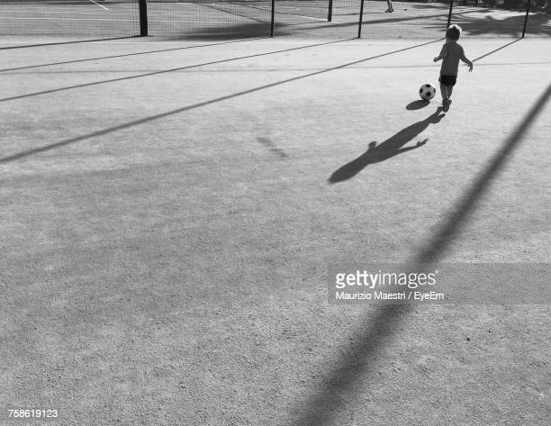 Rear View Full Length Of Boy Playing Soccer On Field During Sunny Day