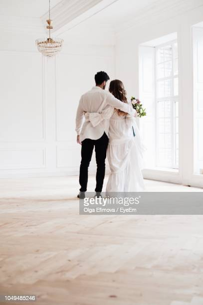 rear view full length of bride and bridegroom standing in room - newlywed stock pictures, royalty-free photos & images